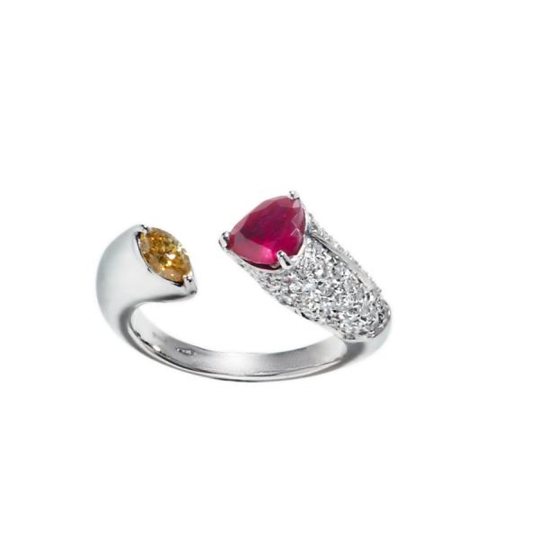 Bague ouverte en or blanc 18 carats, avec d'un côté un rubis de taille cœur serti de 3 griffes et un pavage de 62 diamants de taille brillant, et de l'autre un diamant jaune de taille navette serti de griffes.