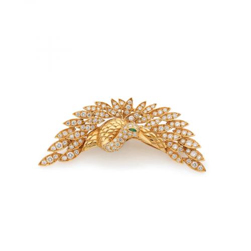 Broche en forme d'oiseau de Paradis en or jaune 18 carats. Le plumage est pavé de diamants de taille brillant, en serti grains. L'œil de l'oiseau est une émeraude de taille navette. La broche mesure environ 6,5 centimètres de largeur.
