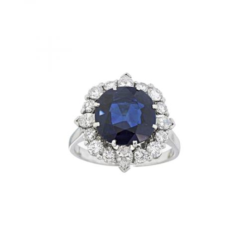 Bague entourage en platine sertie d'un saphir bleu taille coussin entouré de diamants taille brillant et navette.