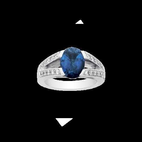 Bague ouverte double branche en or blanc 18 carats sertie d'un saphir bleu ovale avec un pavage de diamants.