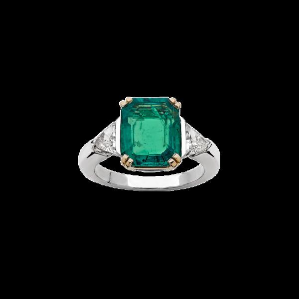 Bague en or blanc et or jaune 18 carats sertie d'une émeraude taille rectangulaire à pans coupés accompagnée de deux diamants taille triangle.