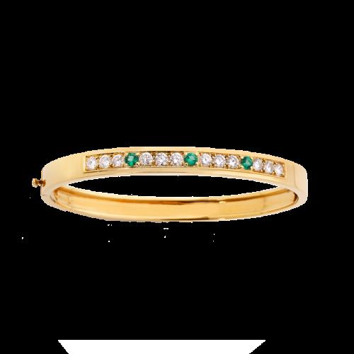 Bracelet jonc ouvrant en or jaune 18 carats serti de 12 diamants brillants et de 3 émeraudes rondes.
